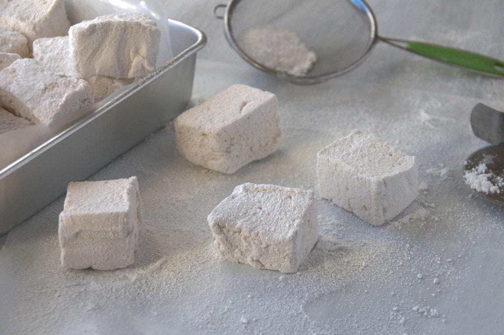 closeup of four marshmallows with Honey Vanilla Marshmallows piled in a parchment lined silver cake pan to the left side and sifter with powdered sugar behind it