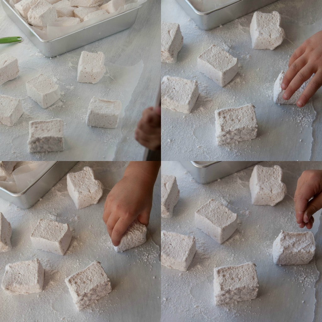 marshmallows being dipped in powdered sugar on parchment paper