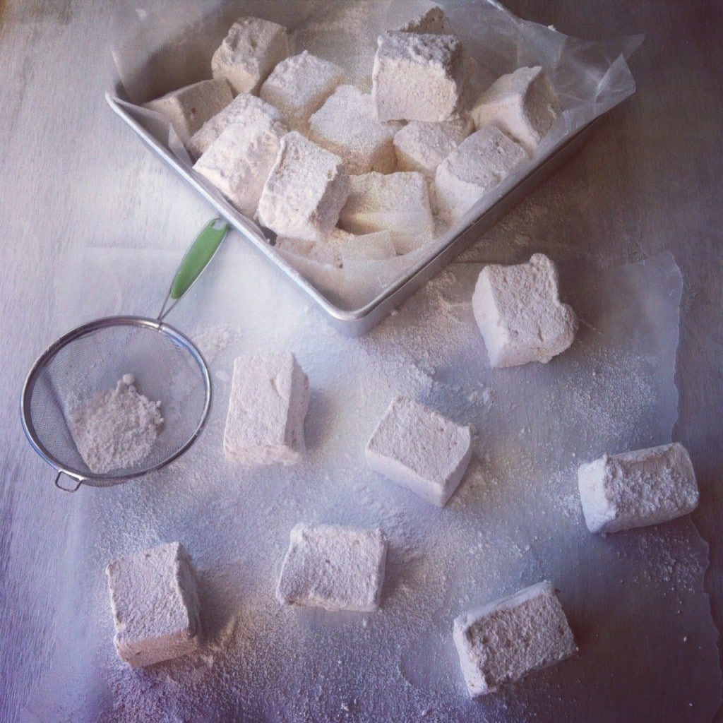 Marshmallows piled in a parchment lined silver cake pan above seven marshmallows covered in powdered sugar next to sifter with powdered sugar in it