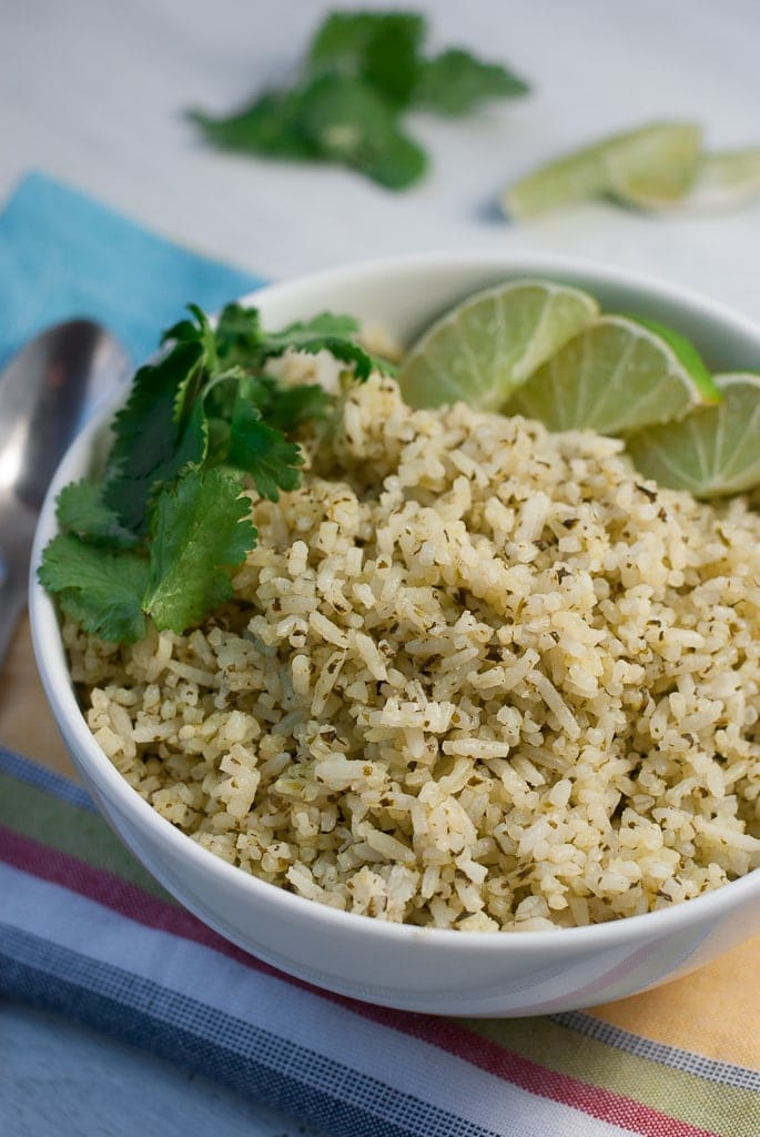white bowl with green cilantro lime rice limes and fresh cilantro
