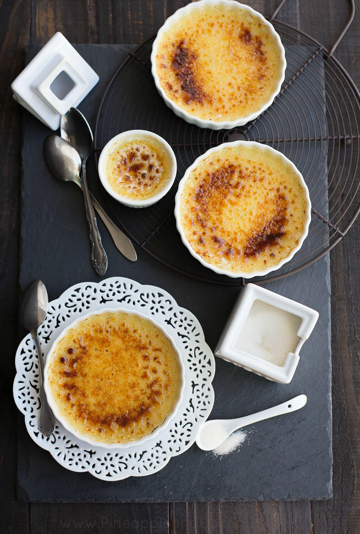 yellow custard creme brulee in white ramekins spoons white sugar bowl black slate board