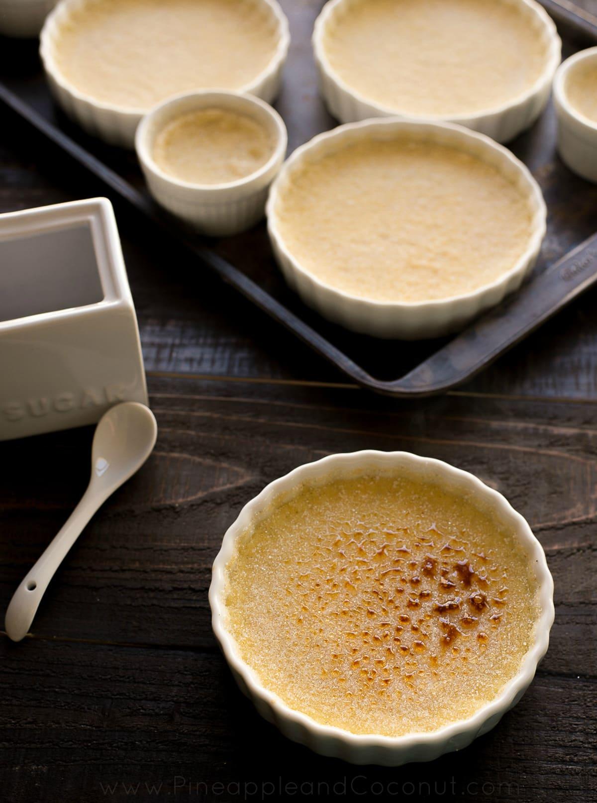 yellow custard in white ramekins spoons white sugar bowl