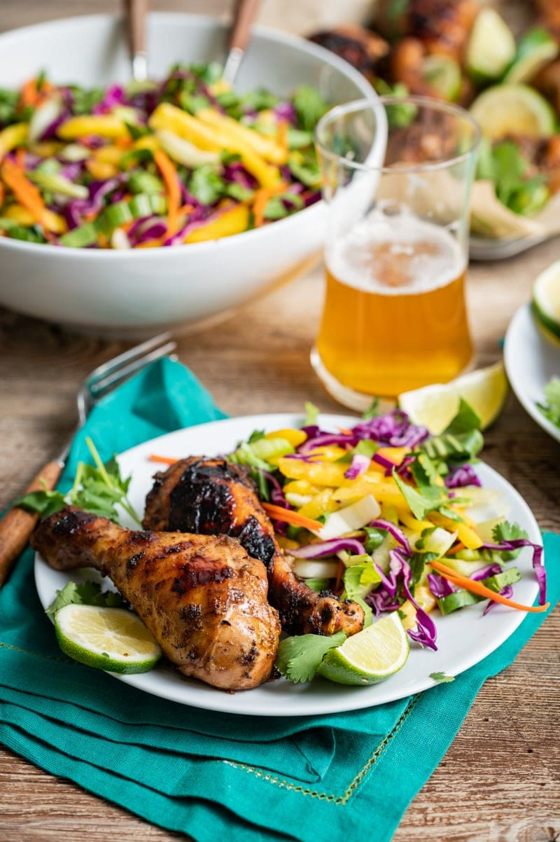 white plate with seasoned grilled chicken drumsticks, large bowl of slaw, glass of beer
