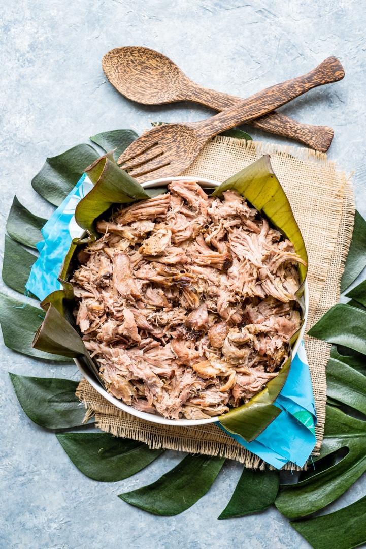 shredded hawaiian slow cooker kalua pork in bowl with banana leaves, wooden utensils, monstera leaf, blue hawaiian print napkin.