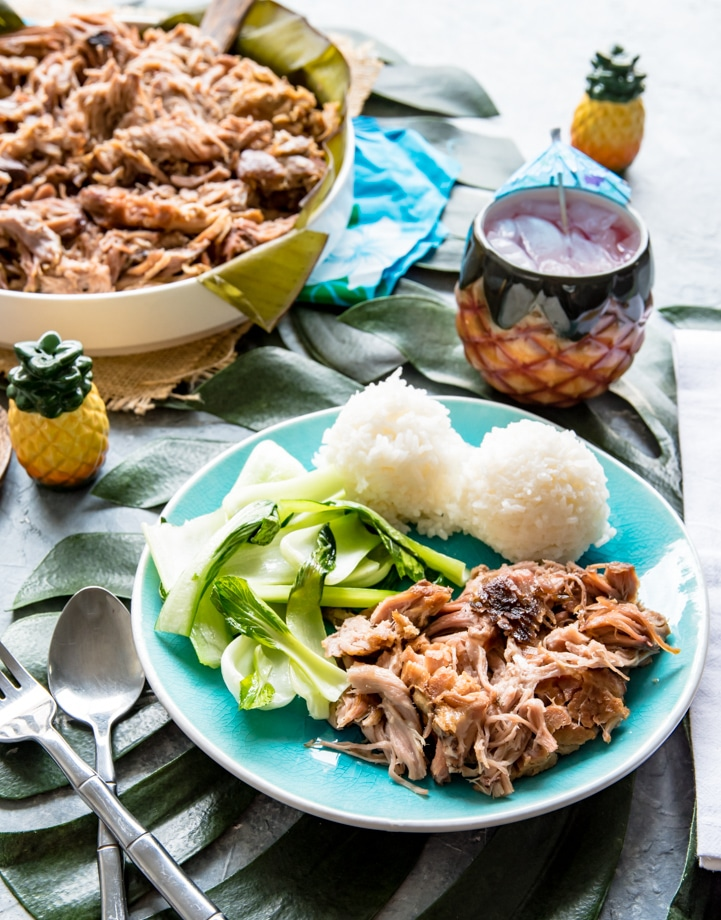 large bowl with shredded kalua pork, small blue plate with serving of kalua pork, scoops of white sticky rice, pineapple wedges, baby bok choy, napkin with hula girl, pineapple salt and pepper shakers.