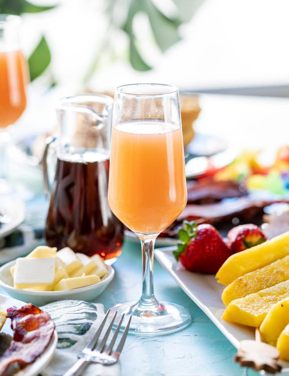 Guava Mimosa in a glass, pineapple spears on plate next to drink, butter on a dish, glass bottle of maple syrup
