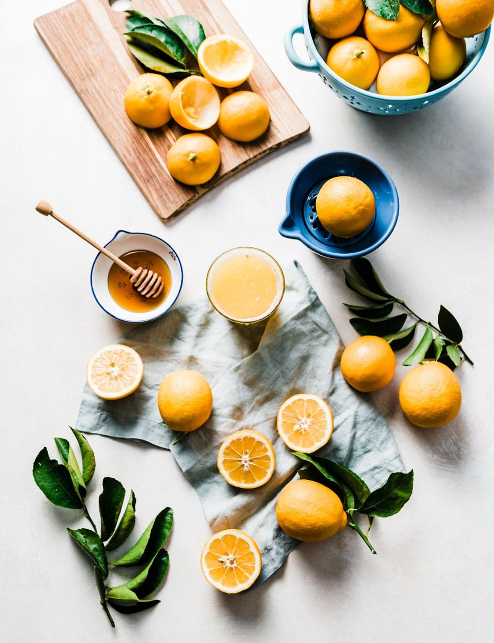cut and whole lemons, cutting board with lemons, blue bowl filled with lemons, lemon leaves, honey in a small bowl with honey stick, glass of lemon juice