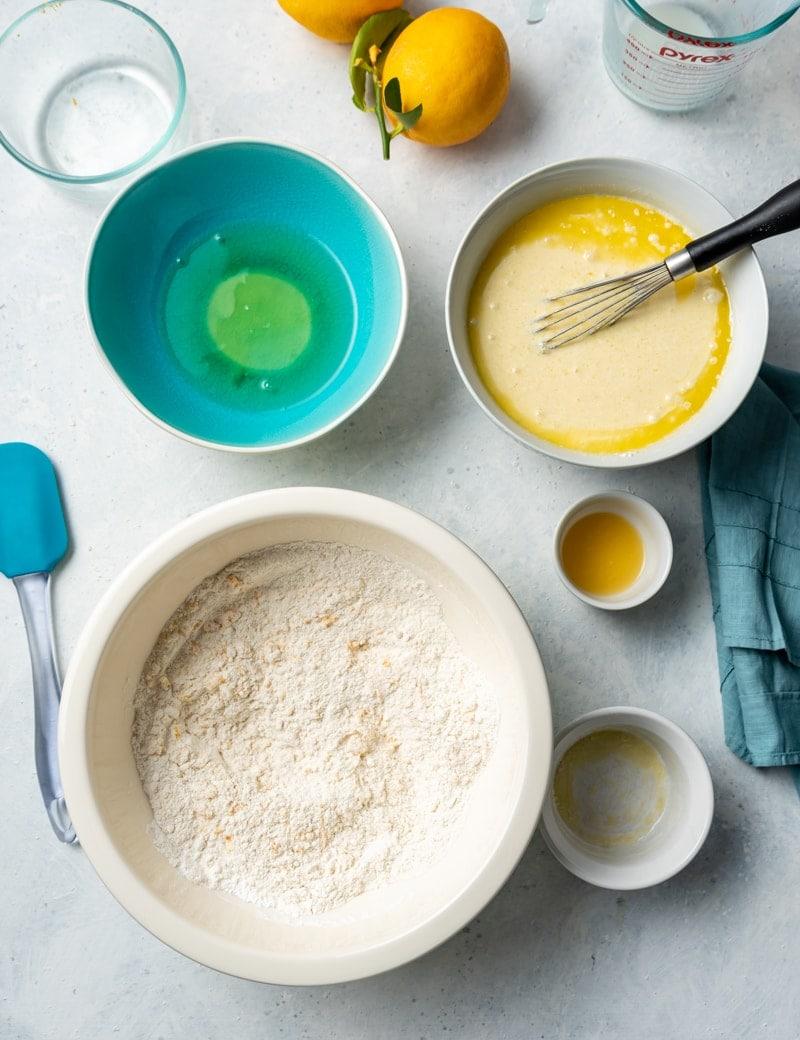 Lemon waffle step by step image large white bowl with flour mixture, aqua bowl with egg whites, white bowl with egg yolks and milk mixture