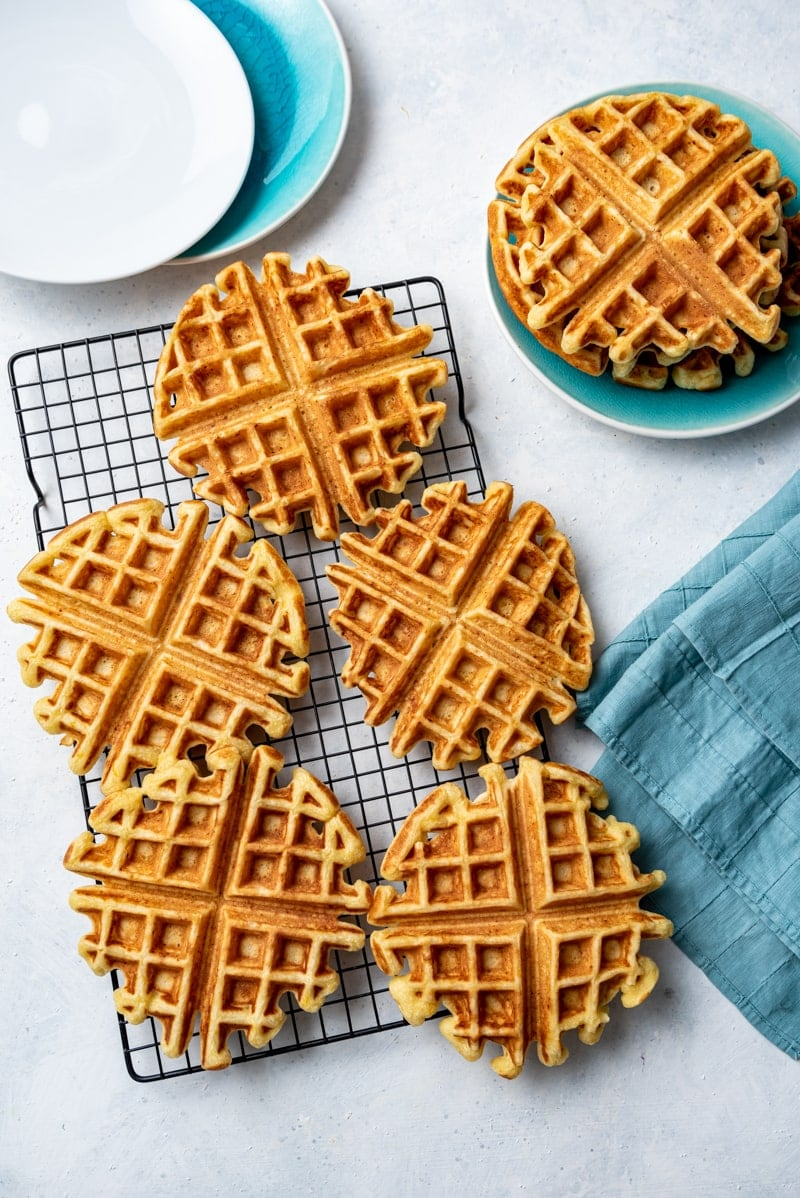 whole cooked lemon waffles on a cooling rack, one waffle on an aqua plate