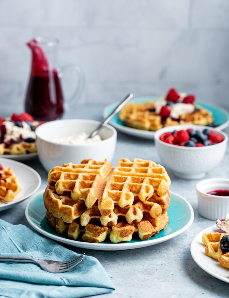 Stack of lemon ricotta waffles on aqua plate, white bowl with whipped cream white bowl filled with raspberries and blueberries, glass bottle with dark red fruit syrup
