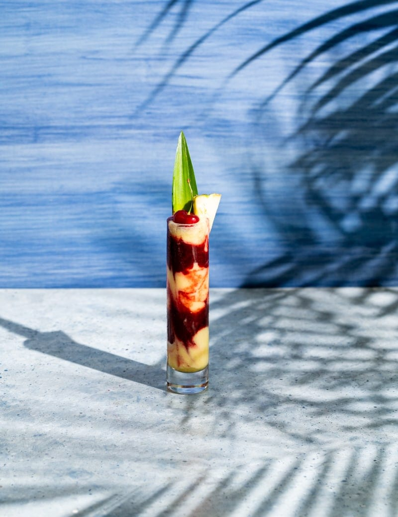 tall skinny glass with alternating layers of yellow and red frozen cocktail, cherry and pineapple leaf in glass