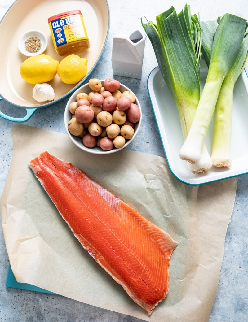 sockeye salmon fillet on paper, tray with three whole leeks, bowl of baby potatoes, aqua pan with lemons, spices, garlic, cream container