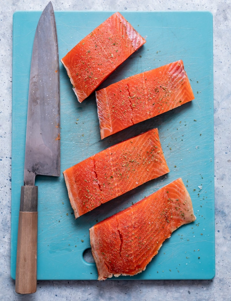 aqua cutting board with four salmon fillets, large knife
