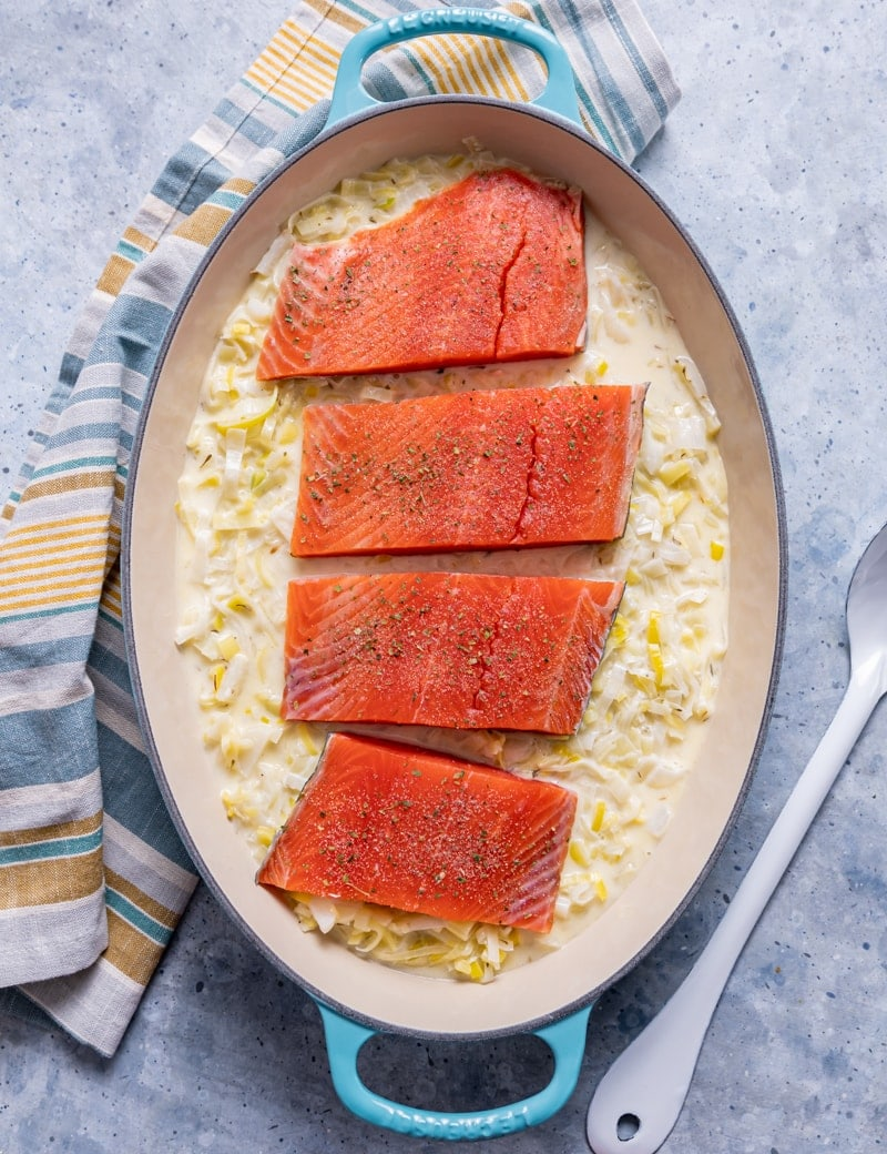 oval aqua cast iron skillet with raw sliced leeks in cream sauce, raw seasoned salmon over the leeks, yellow and blue striped napkin, white spoon