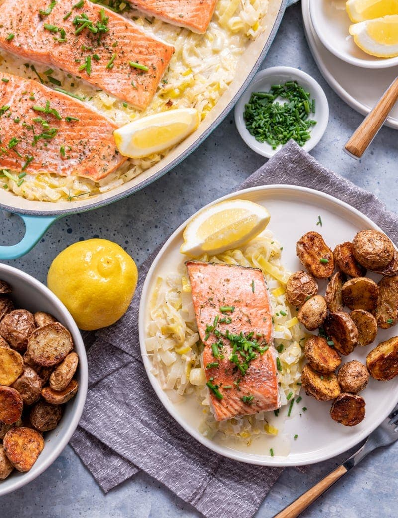 white plate with a piece of salmon over leeks, potatoes on plate as well as a bowl to the side of the dish, whole lemon, lemon slices, large pan of salmon fillets over leeks