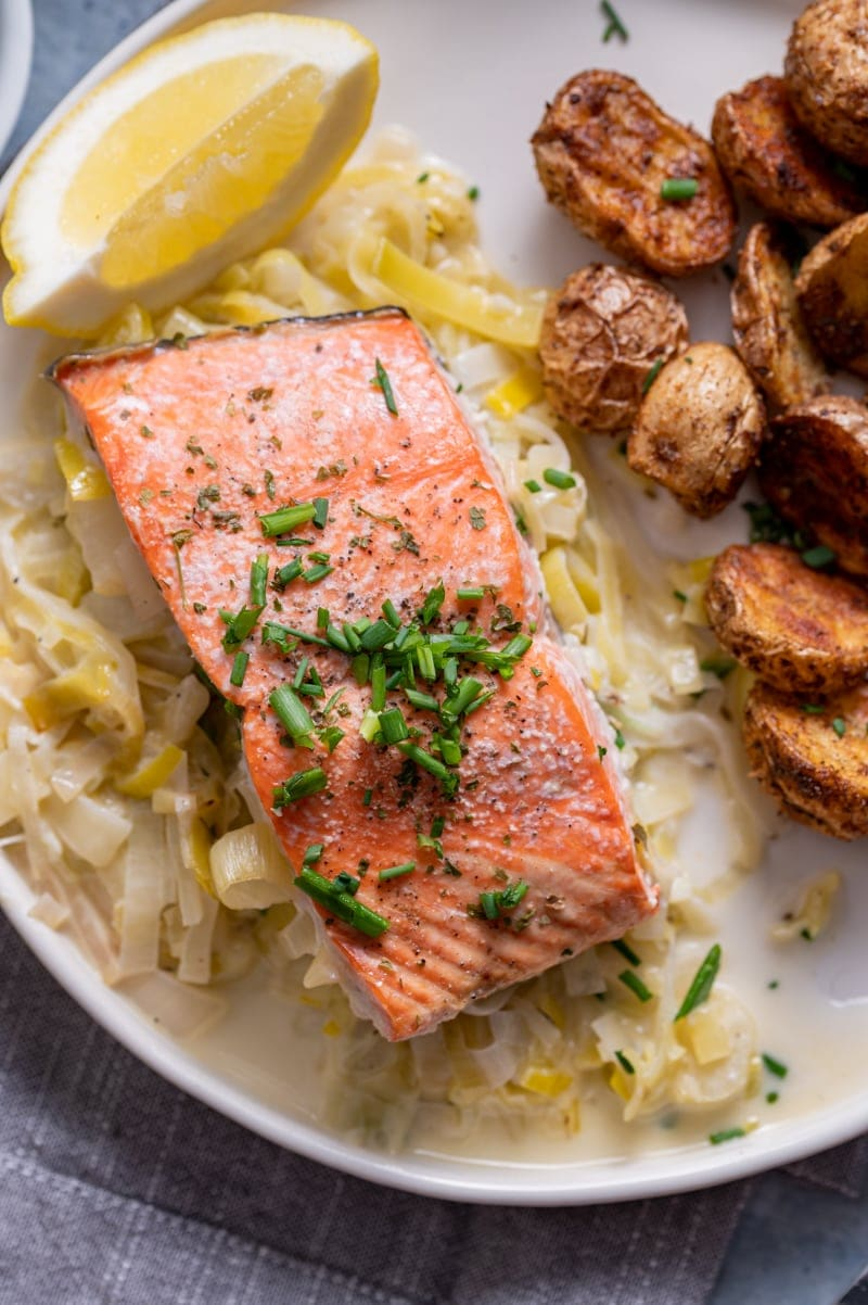 close up of a salmon fillet on top of a serving of cooked creamed leeks, lemon slice, old bay roasted baby potatoes