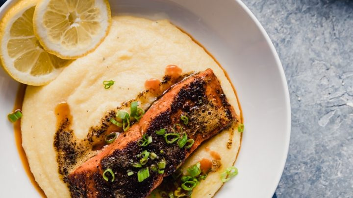 White bowl with yellow grits, seasoned salmon fillet, lemon slices in bowl, gray background, navy blue napkin
