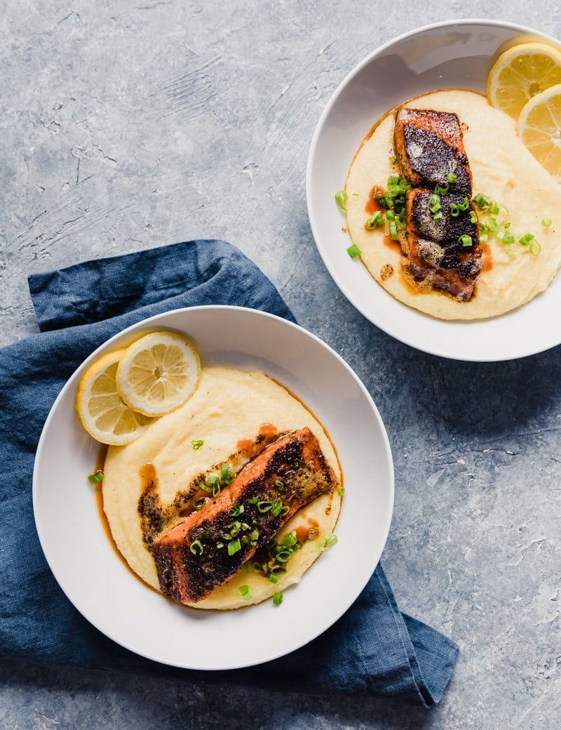Beautiful food photography of wild alaskan salmon served over cheddar cheese grits with lemon slices