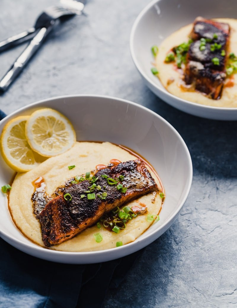 angled photo of two white bowls of wild sockeye salmon fillets served over cheddar grits with hot sauce and lemon slices