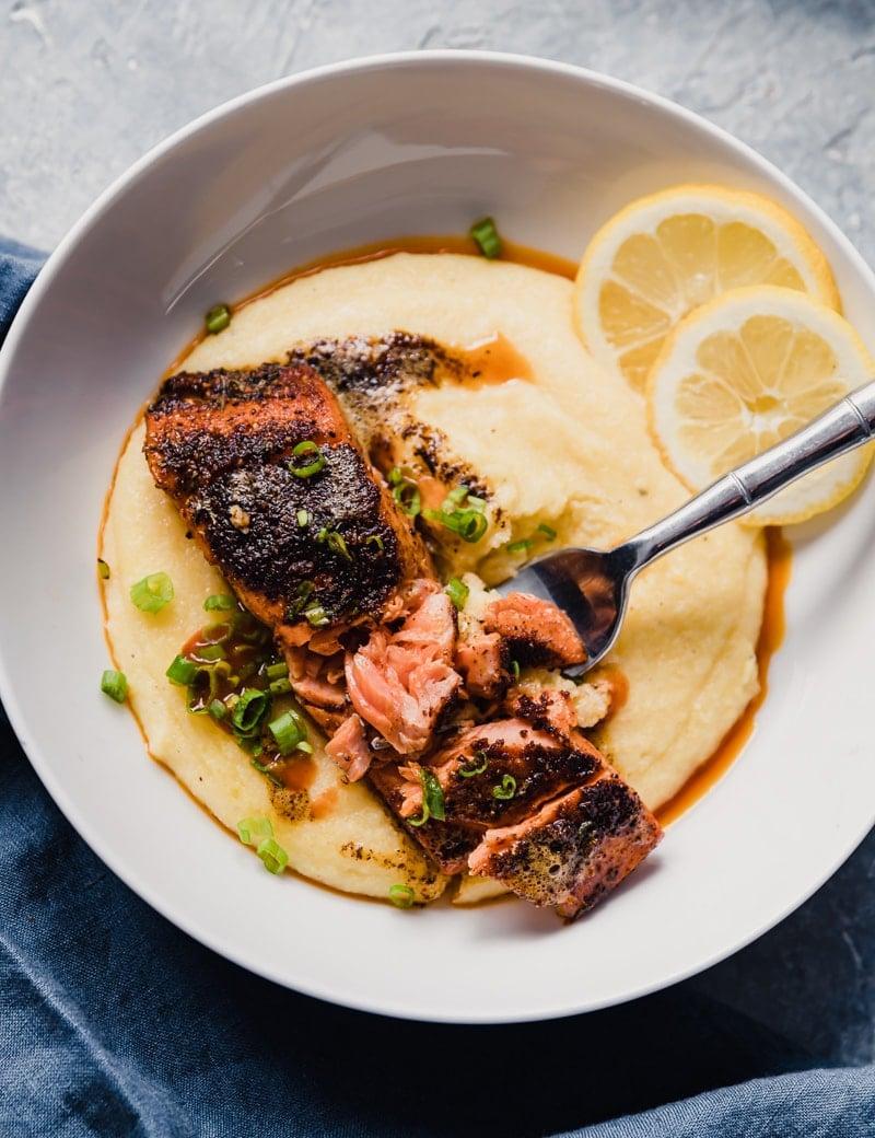 Closeup overhead food photo of wild alaskan sockeye salmon with cajun seasonings served over creamy grits with lemon and hot sauce