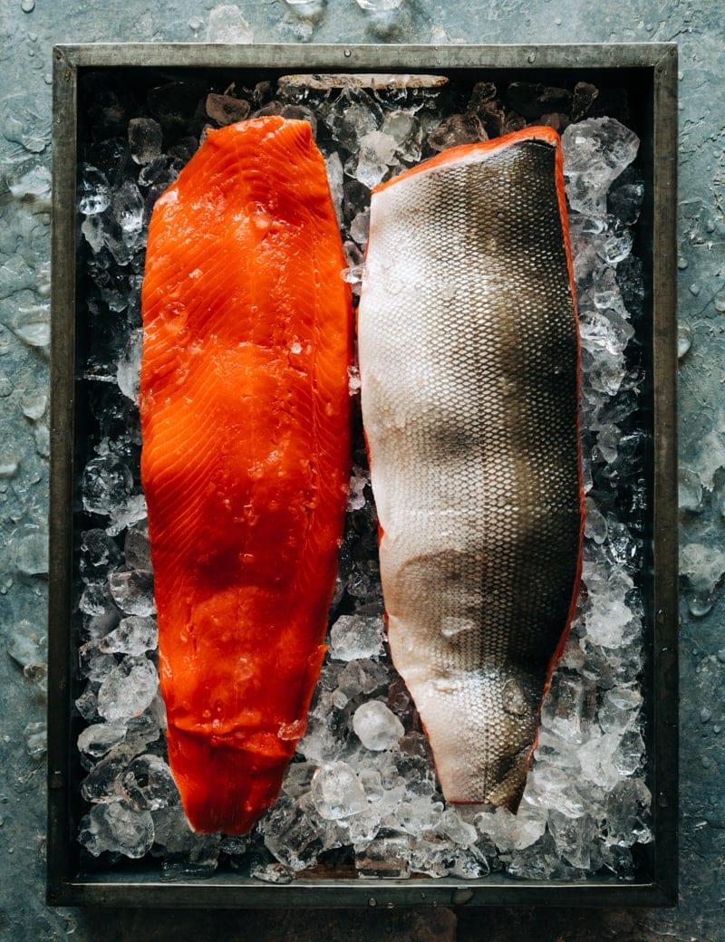 Two wild Alaskan sockeye salmon fillets on ice in a tray