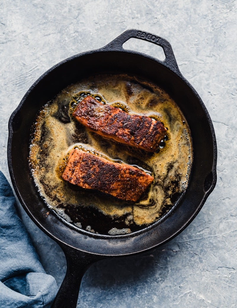 two cooked wild sockeye salmon fillets in a cast iron pan with sauce