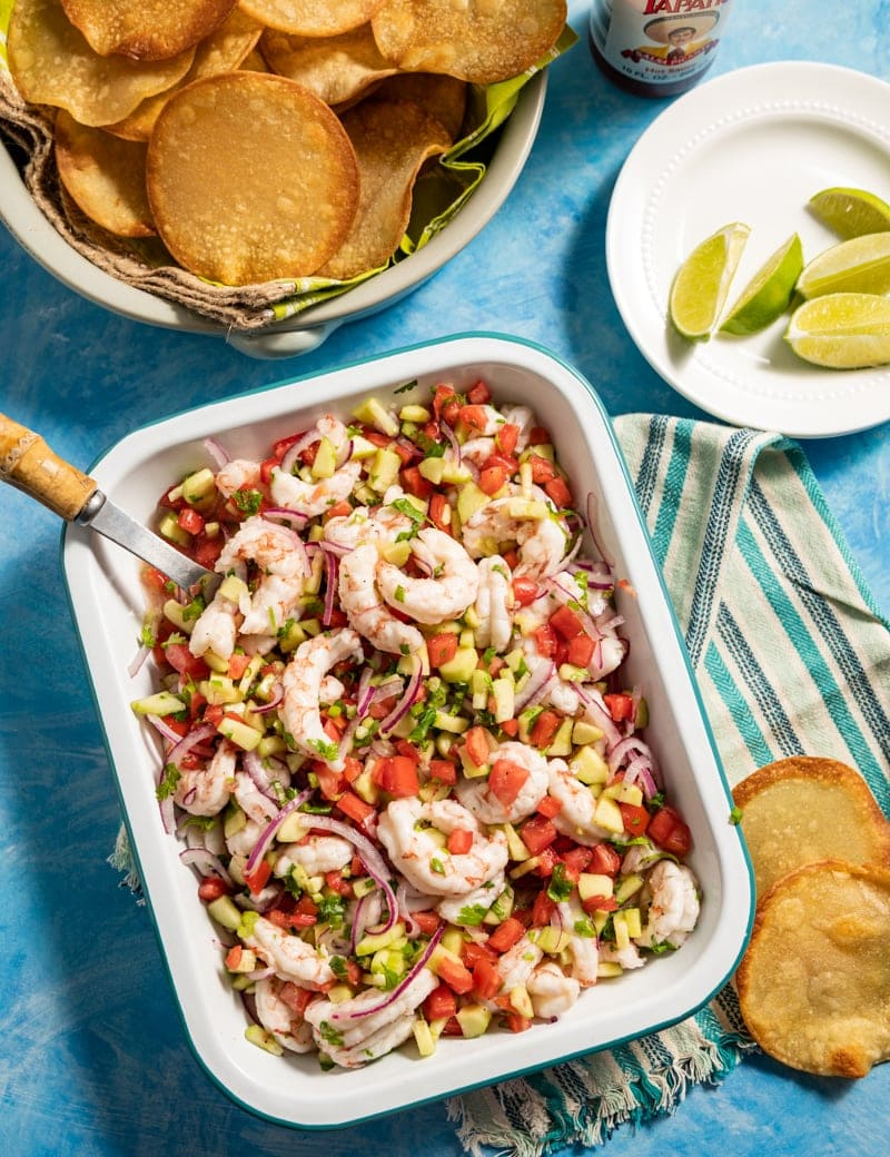 Mini Shrimp Ceviche Tostadas prep pic with mini tostadas in a basket, shrimp ceviche in a pan cut limes on a plate
