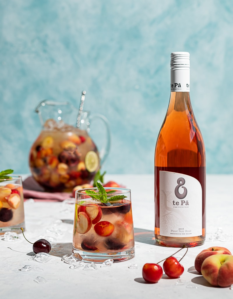 Pitcher filled with cherries and peaches and wine, two glasses filled with ice, wine, fruit, cherries and peaches scattered on table, bottle of te pa rosé wine