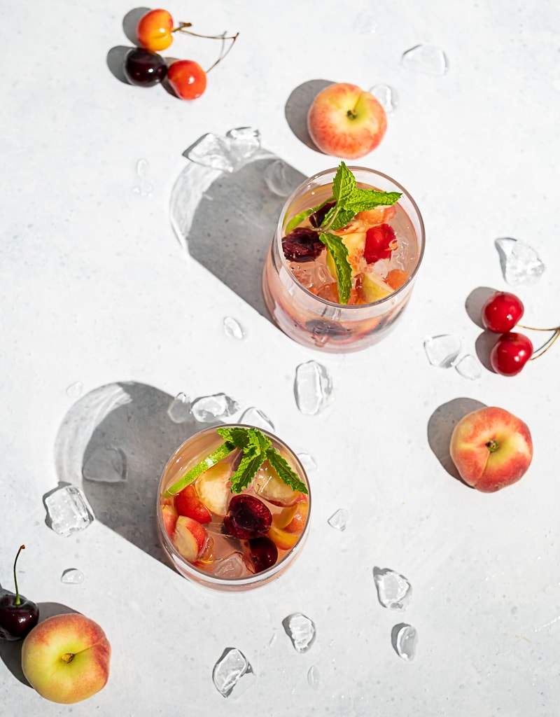 Two glasses filled with ice, wine, fruit, cherries and peaches scattered on table