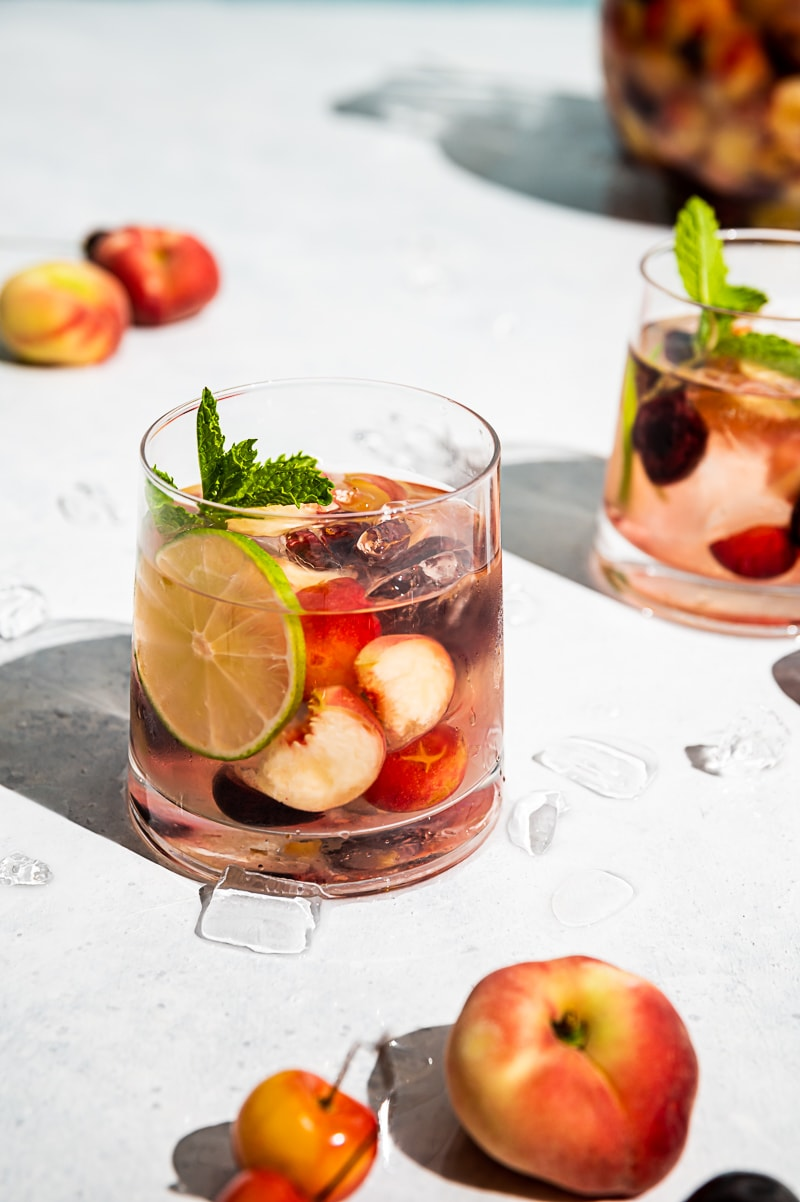 close up of glasses filled with ice, wine, fruit, cherries and peaches scattered on table