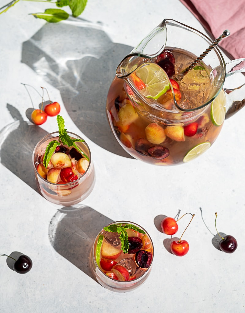 Pitcher filled with cherries and peaches and wine, two glasses filled with ice, wine, fruit, cherries and peaches scattered on table