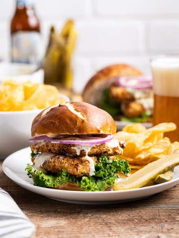 chicken schnitzel sandwiches on pretzel bun with green lettuce red onion kettle chips pickles and glass of beer