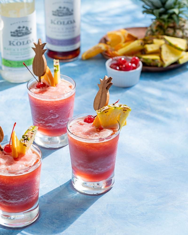 Pink frozen cocktails, pineapple wood cocktail stick, pineapple wedge, orange slice, maraschino cherry, blue background