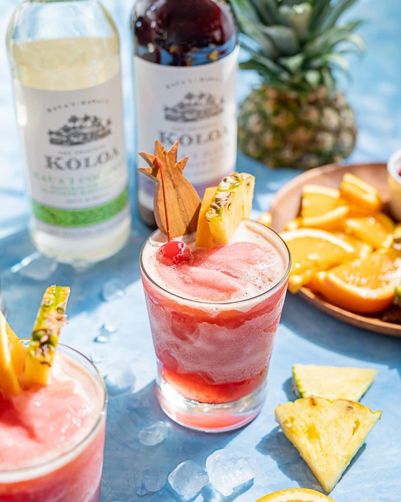 Pink frozen rum runner cocktails, pineapple wood cocktail stick, pineapple wedge, orange slice, maraschino cherry, blue background