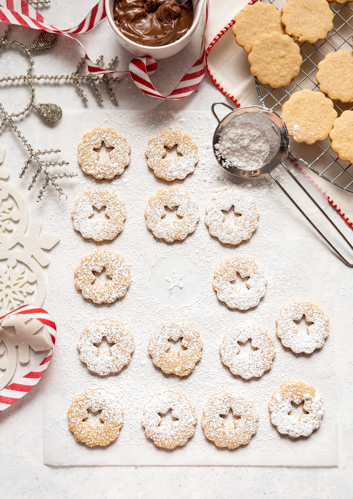 cookies with stars cut out of middle dusted with powdered sugar