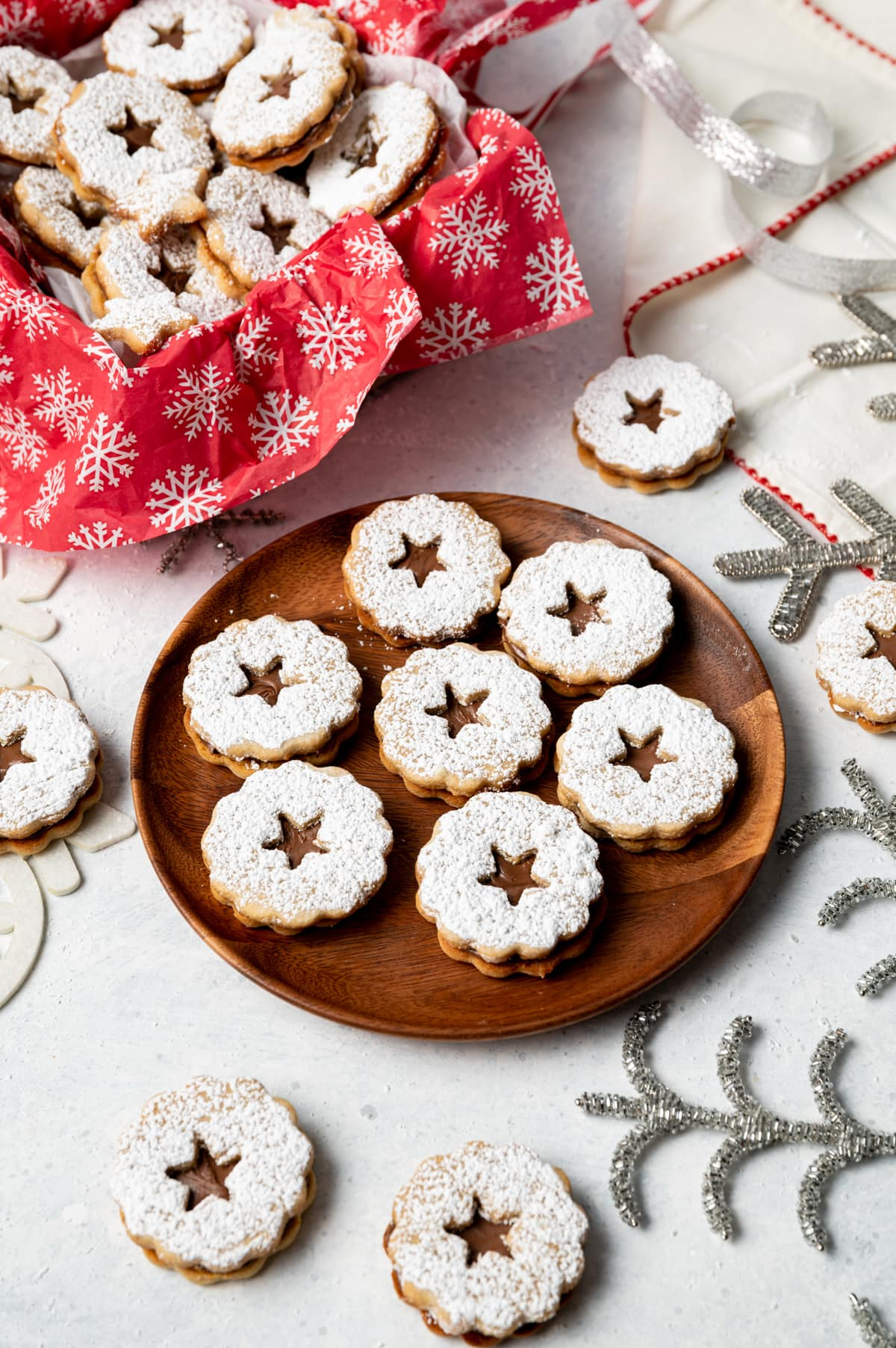 chocolate filled sandwich cookies on a wood plate and chocolate filled sandwich cookies in a box with red and white snowflake paper