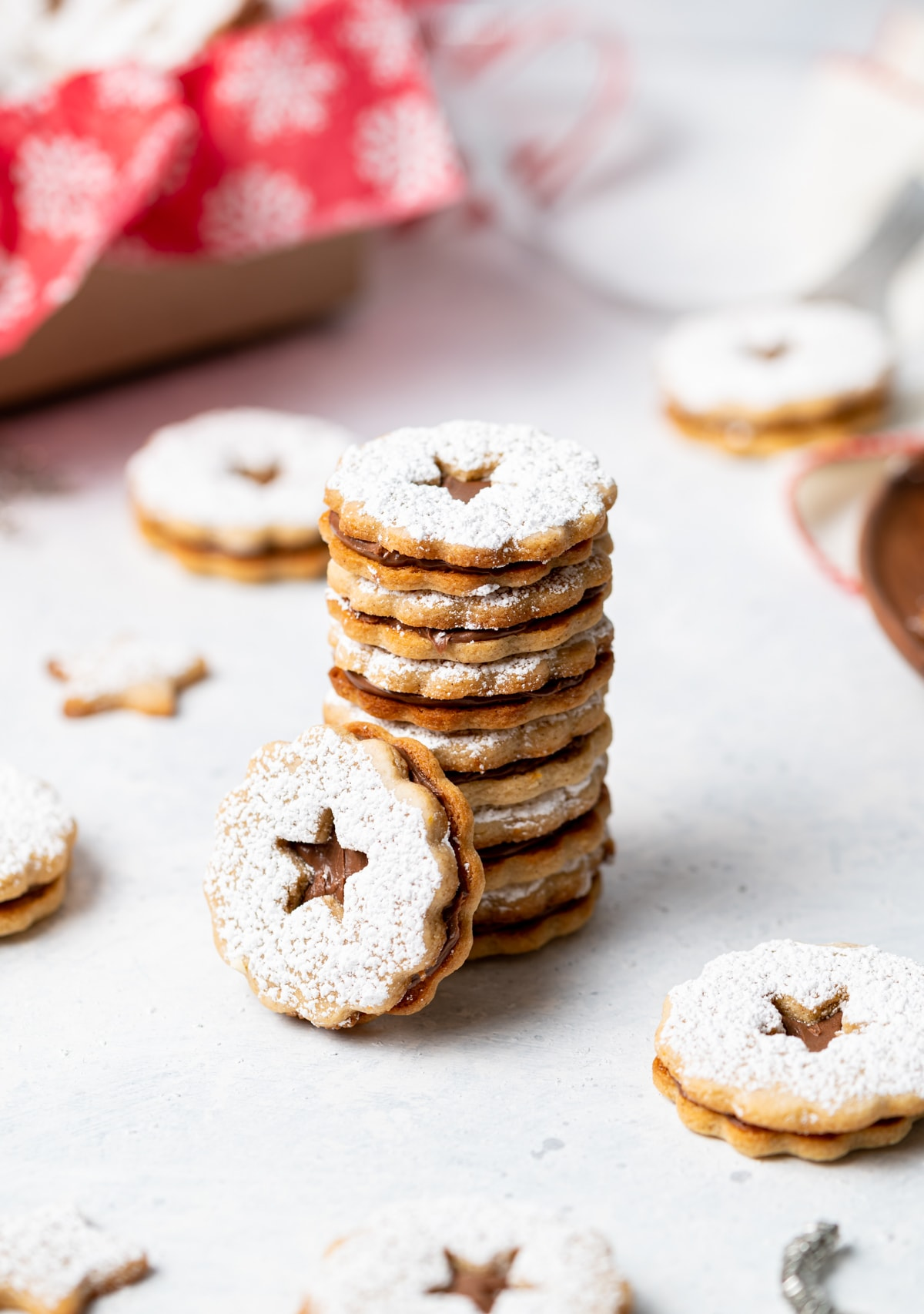 stack of chocolate cinnamon linzer cookies with powdered sugar