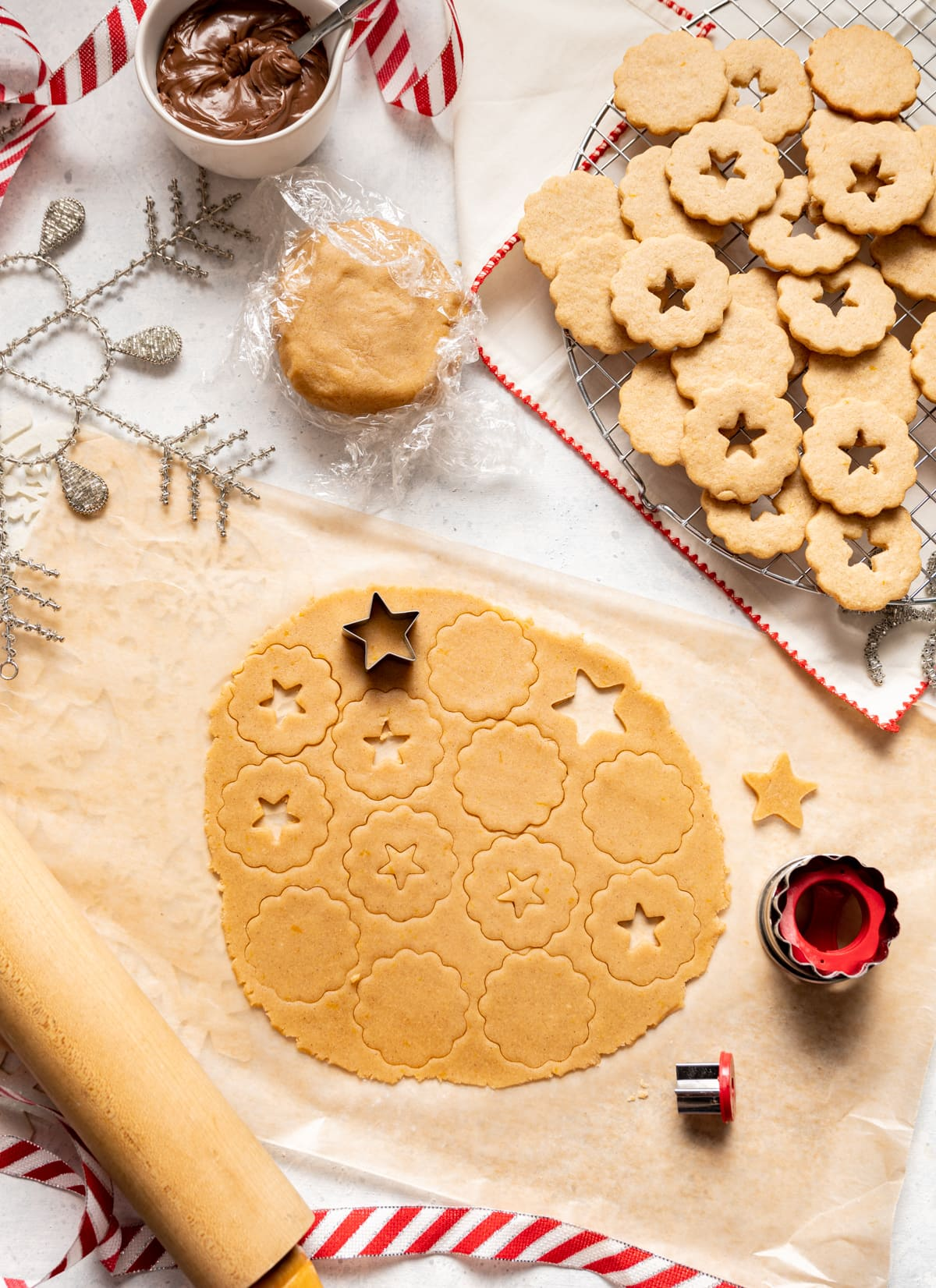 rolled out dough with cookie cut outs, wire rack with cookies cooling, dough rapped in plastic bowl of chocolate spread