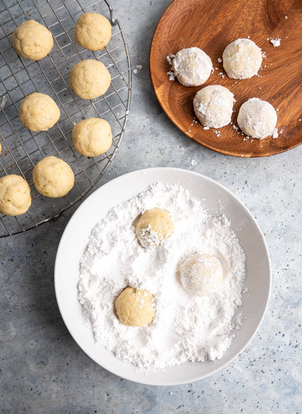 cookies on a wire cooling rack, cookies in a bowl with powdered sugar, cookies covered in powdered sugar on a wooden plate