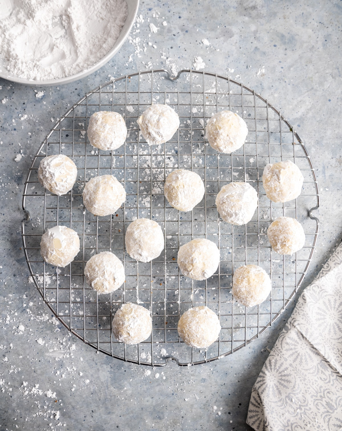 round cookies covered in powdered sugar on a round wire cooling rack