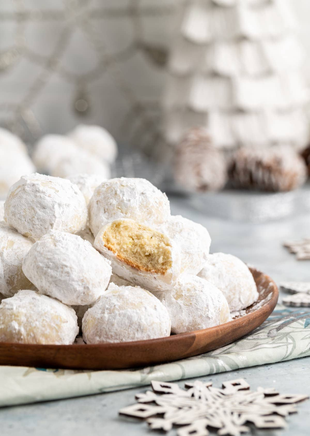 small round cookies covered in powdered sugar on a brown plate