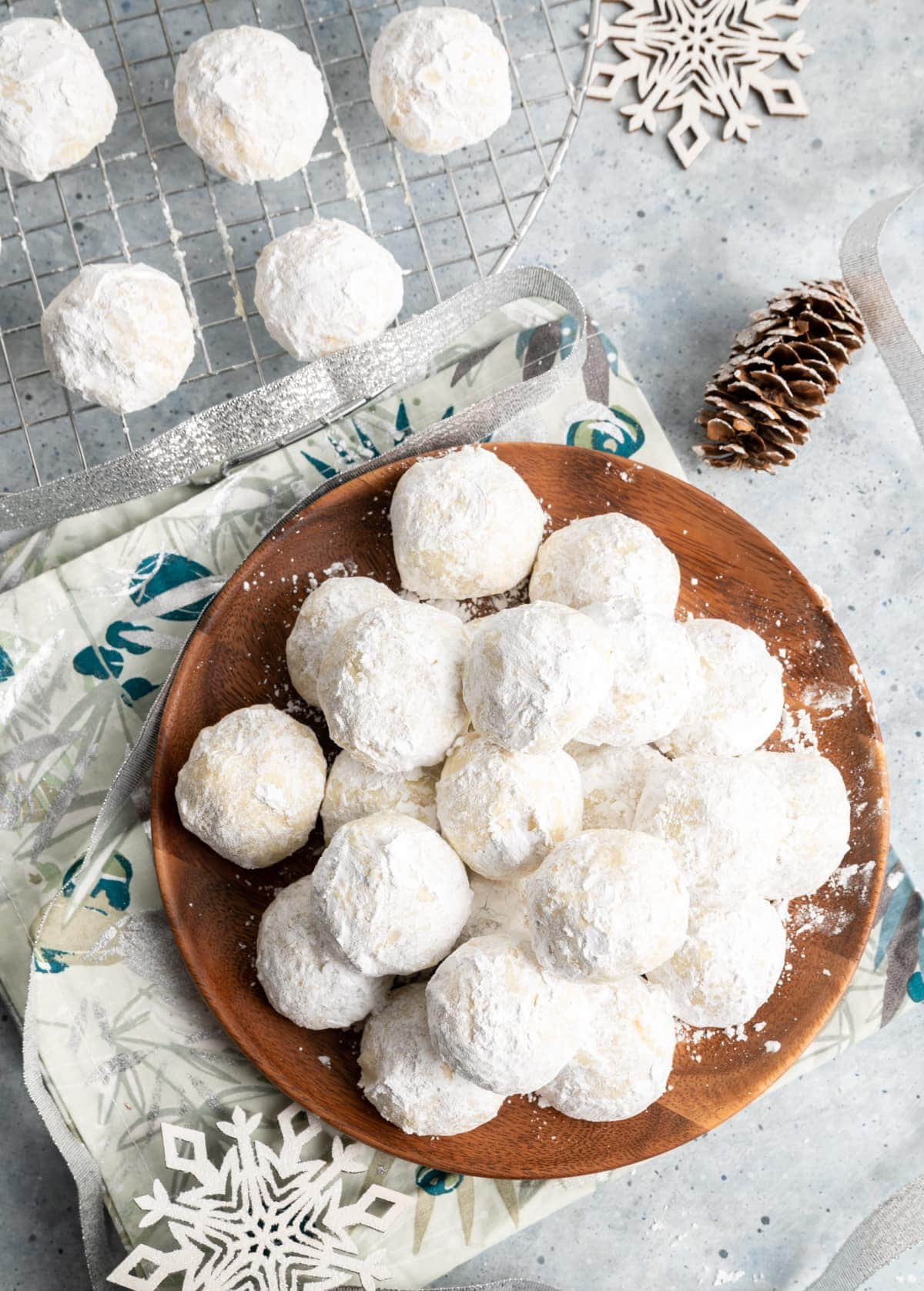 round cookies covered in powdered sugar on a brown plate, wire rack with same cookies, napkin, wood snowflakes, pine cone