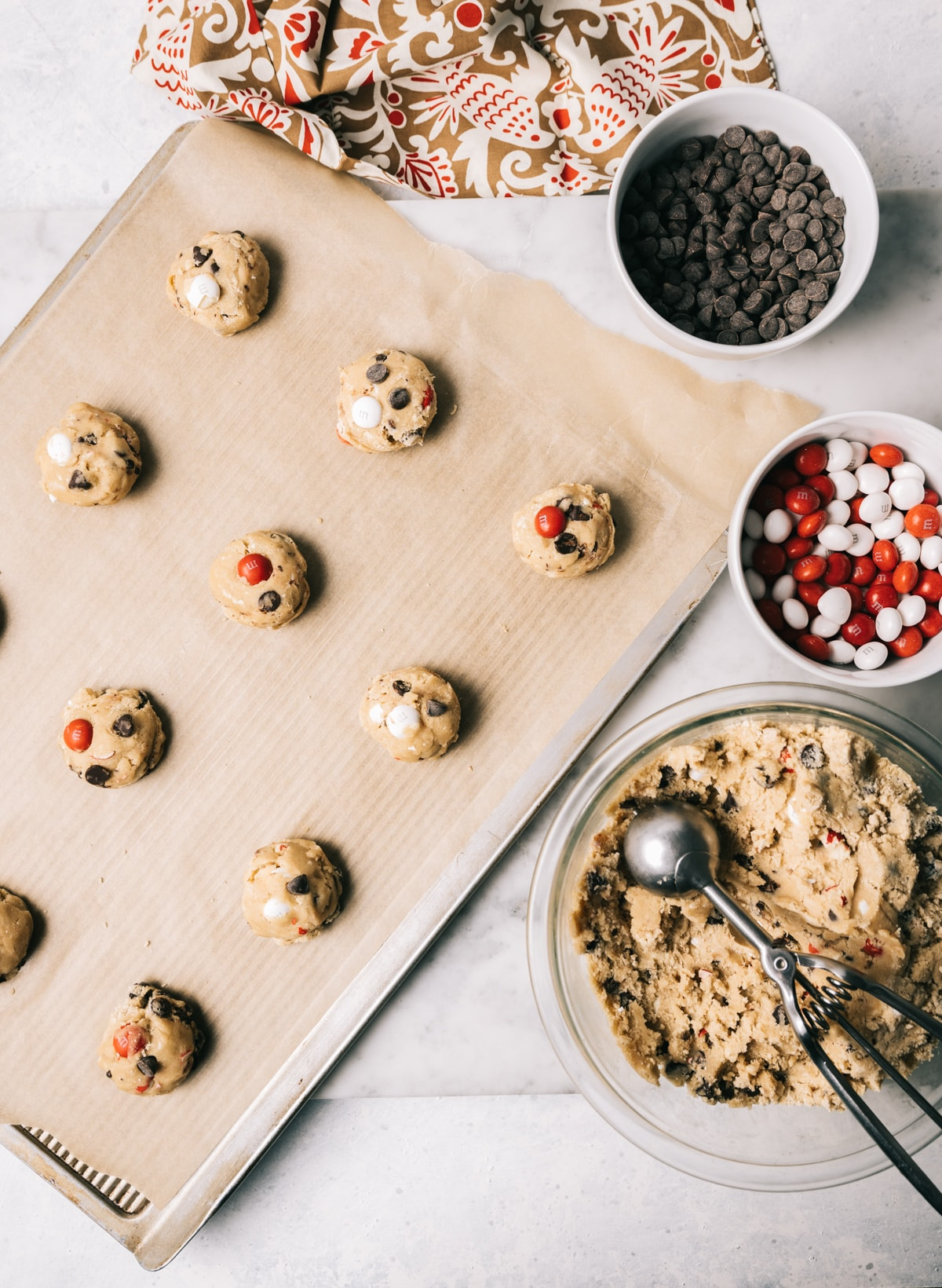 chocolate chip cookie dough balls on a baking tray with parchment paper bowl of cookie dough bowl of M&Ms bowl of chocolate chips