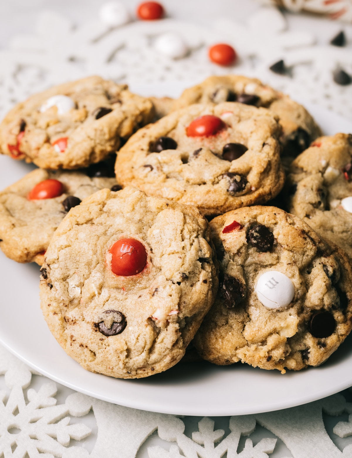 chocolate chip cookies with red and white M&M candies on a white plate