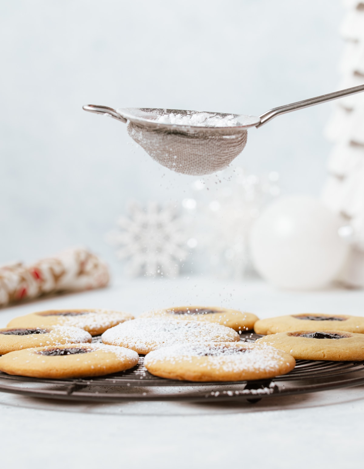 powdered sugar being dusted on round sandwich cookies with dark purple jam layered on a wire rack