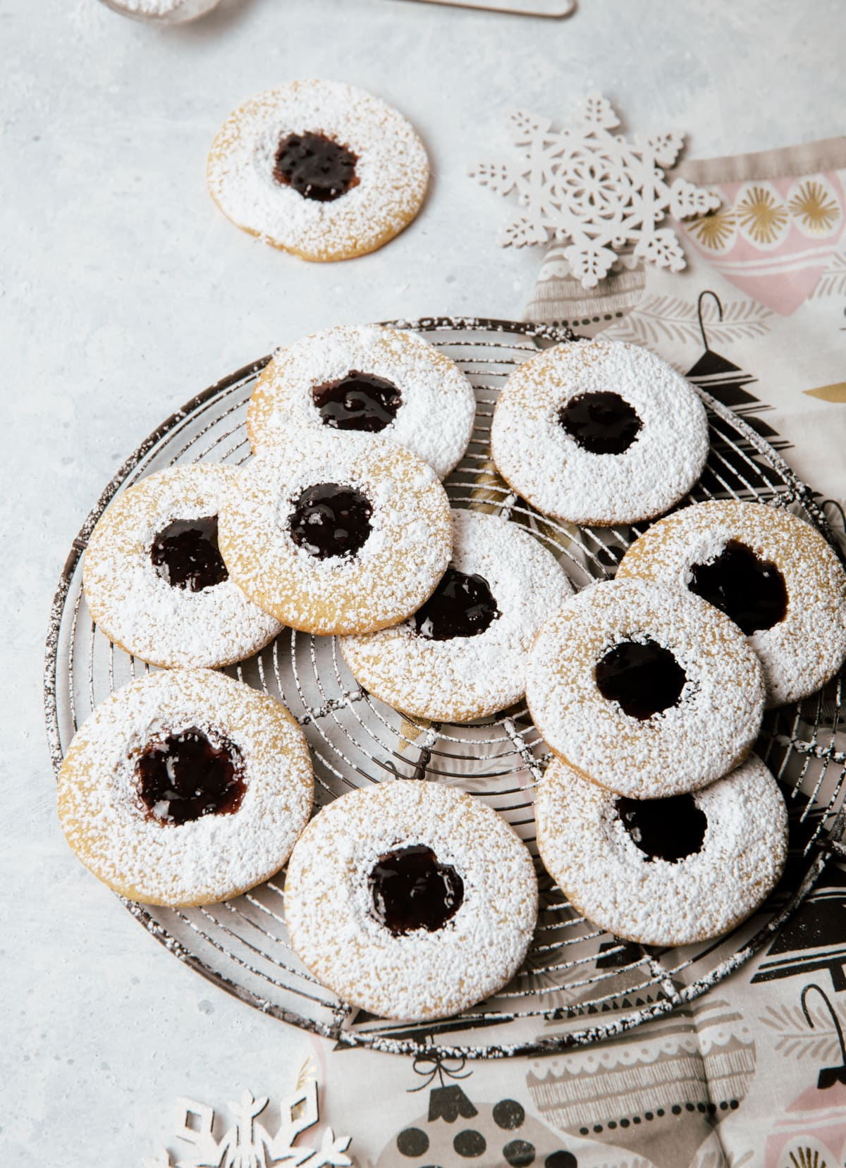 round sandwich cookies with dark purple jam layered on a wire rack