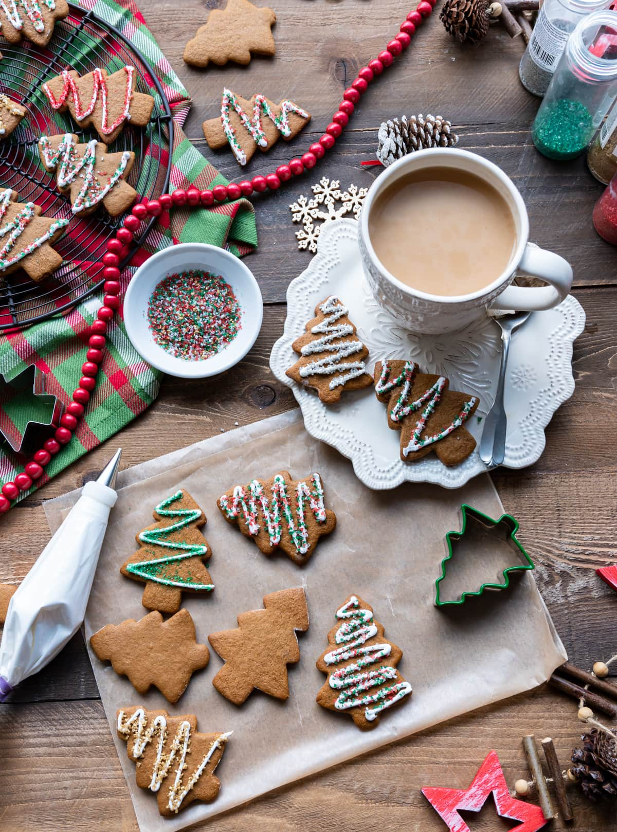 gingerbread christmas tree cut out cookies, cup of tea, cookie cutters, bowl of colored sugar