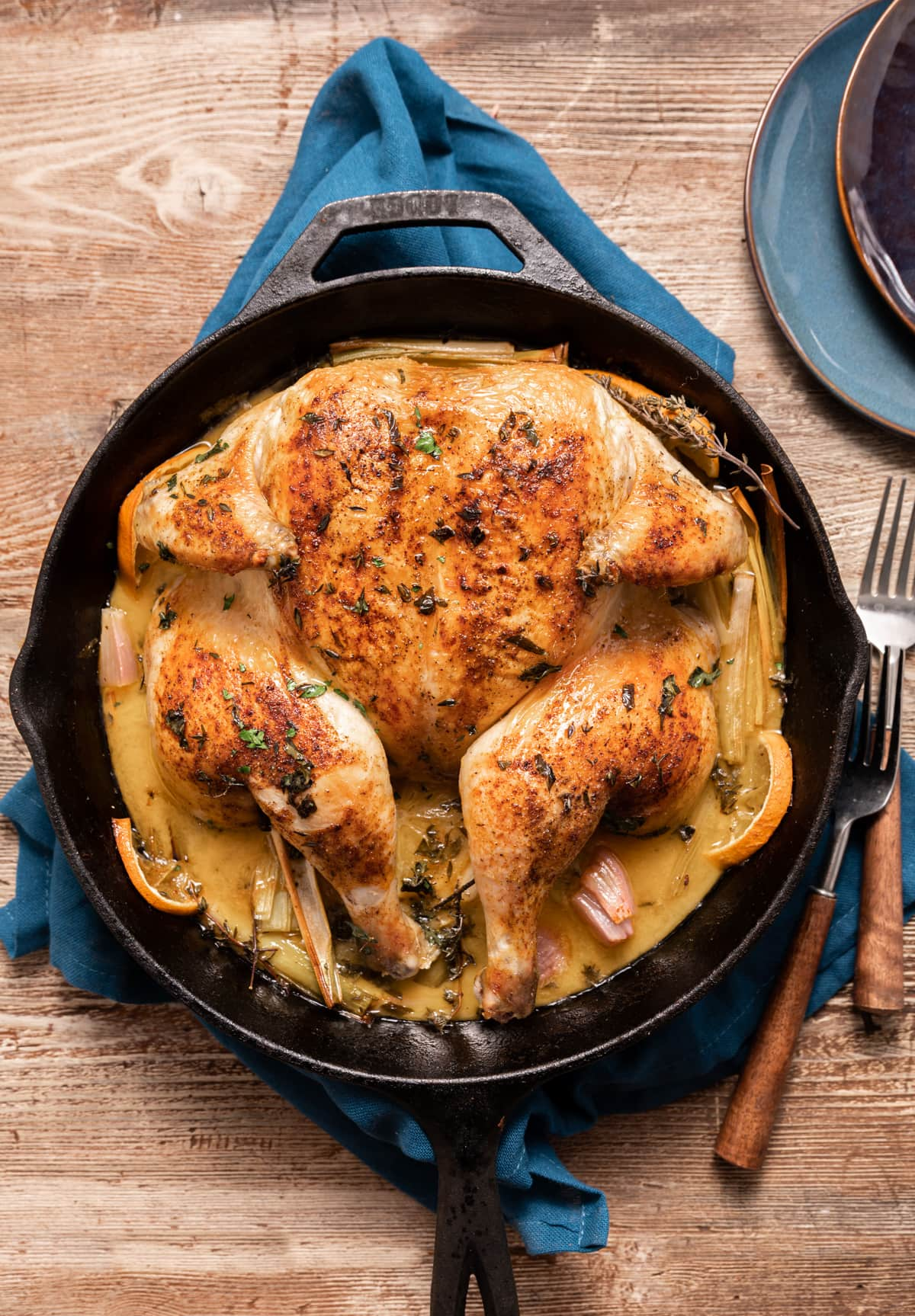 whole roasted chicken in a skillet with lemons and oranges and leeks