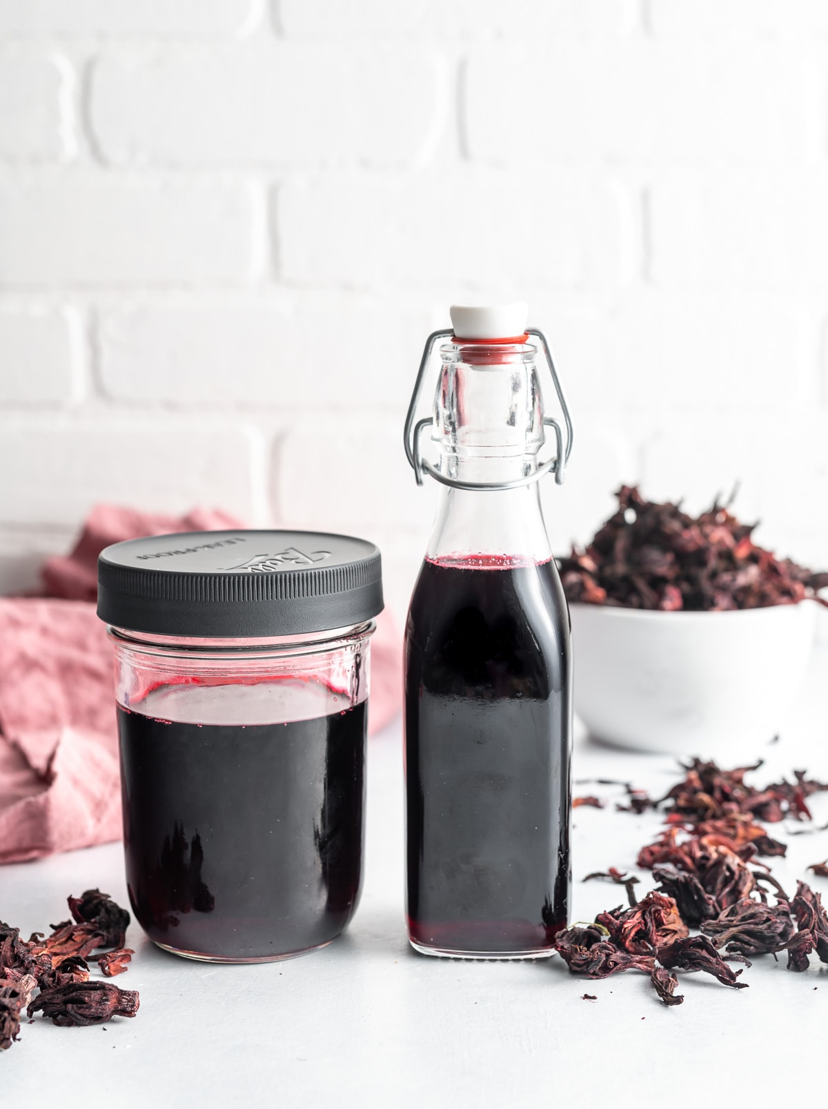 dark red hibiscus simple syrup in a jar and in a bottle scattered dried hibiscus flowers