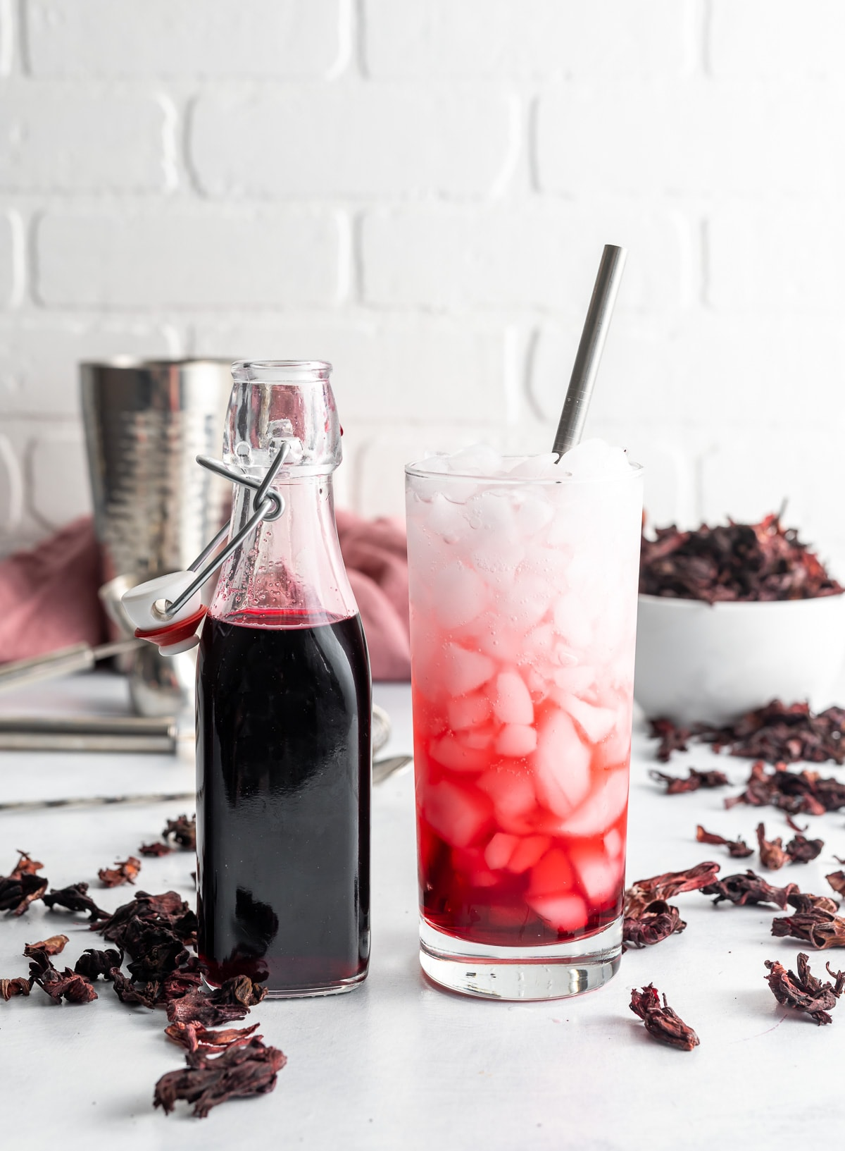 bottle of dark red hibiscus syrup in a bottle glass with ice with syrup and soda